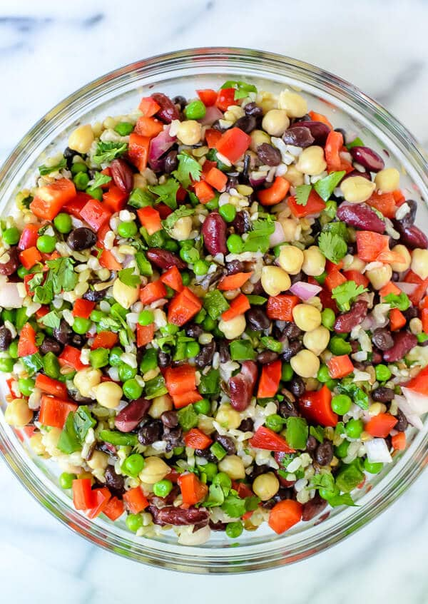 Wild rice, peas, chick peas, black beans and jalapeno salad in a glass bowl
