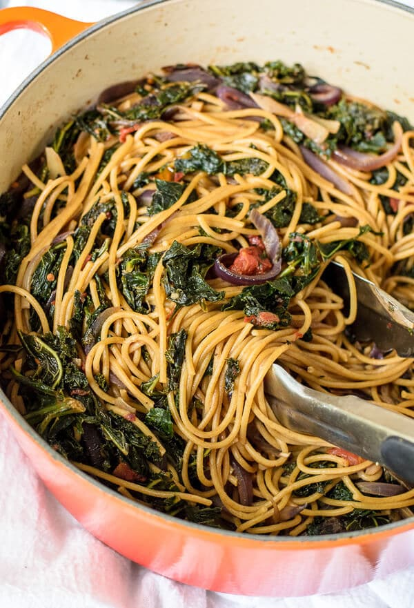 Kale Pasta with Walnuts and Parmesan in a large stock pot with tongs