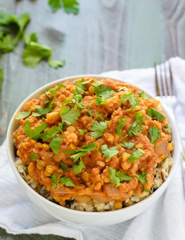 bowl of healthy red lentil curry with cauliflower garnished with cilantro