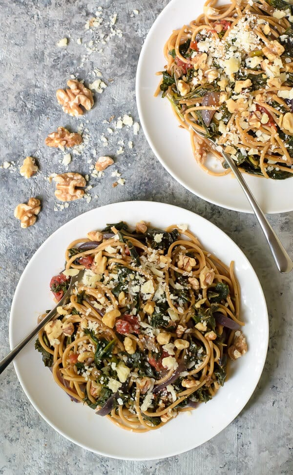 Walnut Kale Spaghetti with Parmesan and Caramelized Onions on white plates with forks