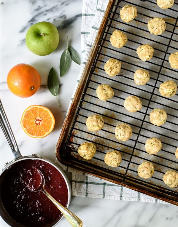 Baked healthy Cranberry Turkey Meatballs on a baking sheet topped with a wire rack beside oranges, apples, sage leaves, and cranberry sauce.