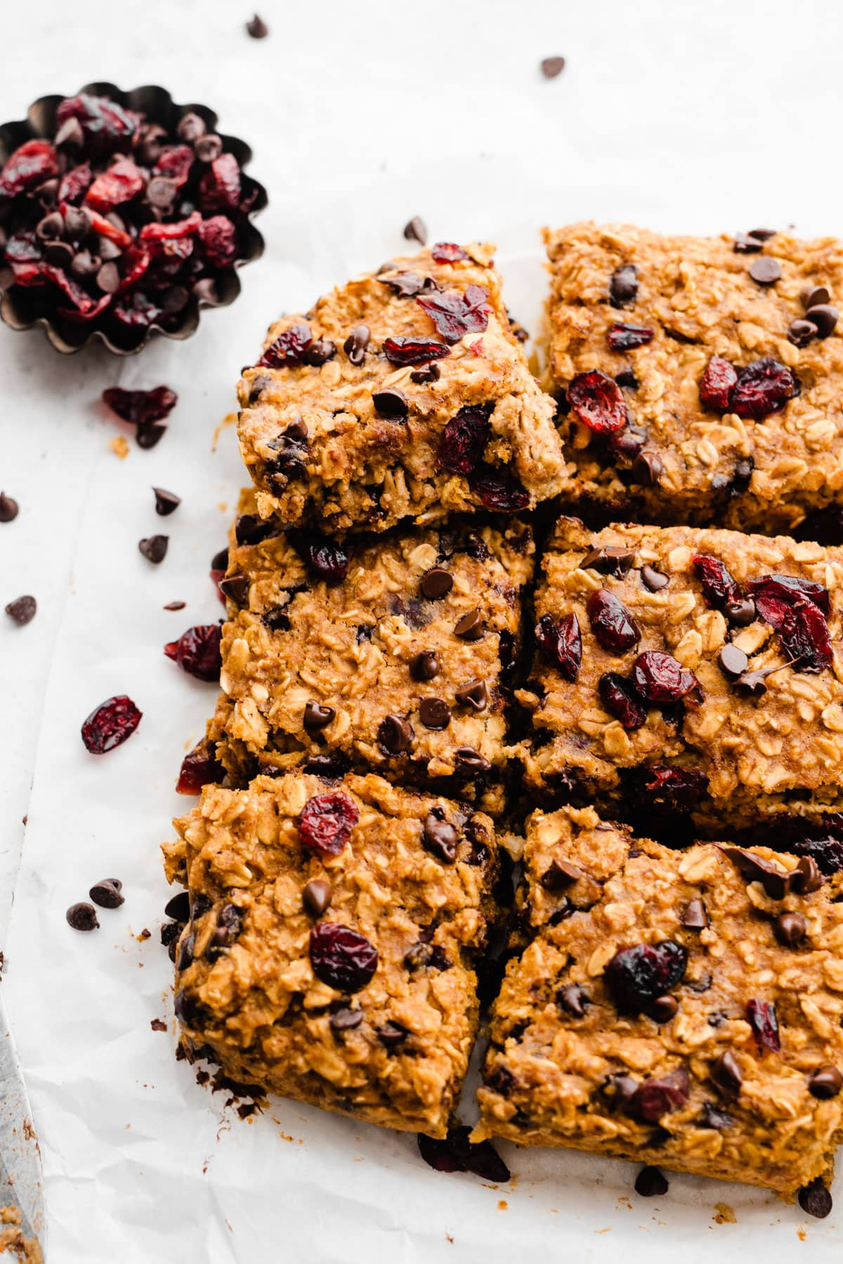 Gluten Free healthy pumpkin bars with cranberries, chocolate chips, and oats cut into squares on parchment paper