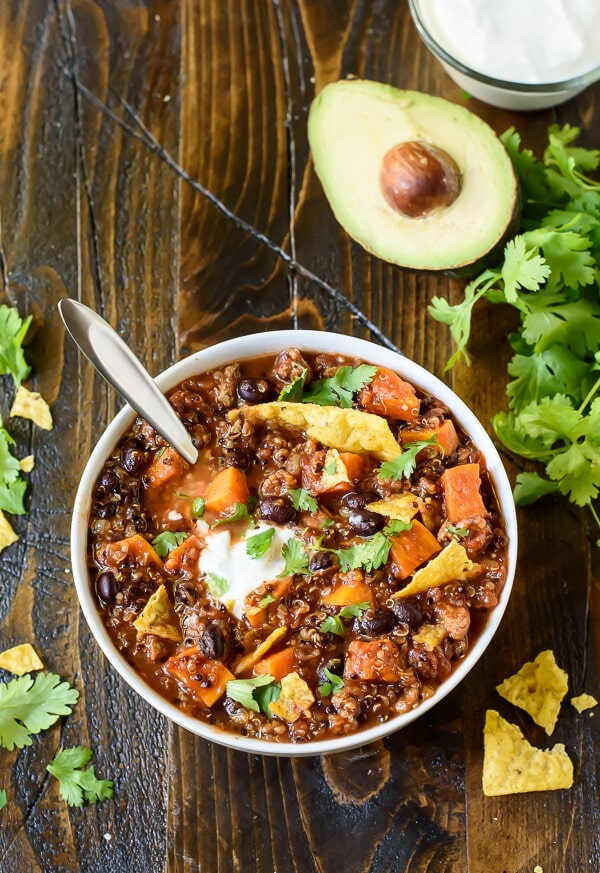 Slow Cooker Turkey Chili with Quinoa and Sweet Potatoes in a white bowl next to fresh avocado