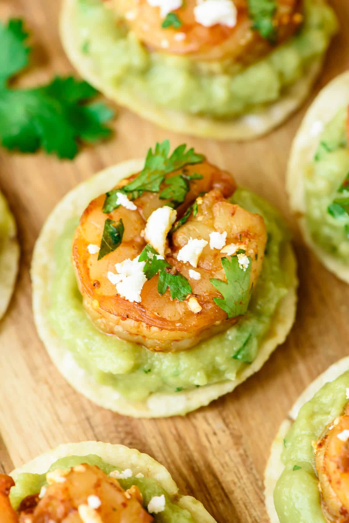 Spicy Shrimp Guacamole Bites - Juicy shrimp and spicy guacamole on top of a crunchy toritlla chip. So EASY and everyone loves this appetizer recipe!