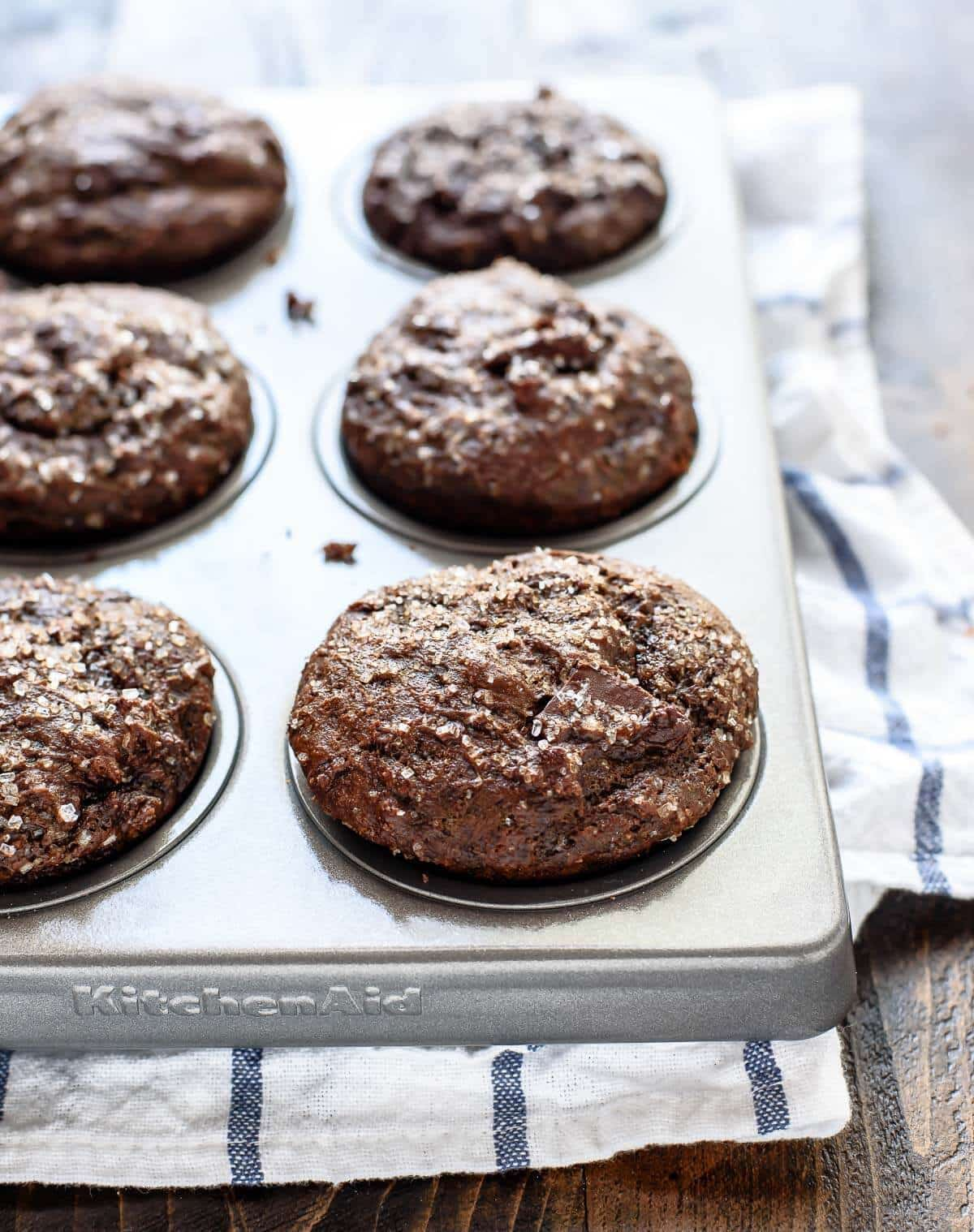 Healthy Chocolate Gingerbread Muffins made with coconut oil, Greek yogurt, and big chunks of dark chocolate. Every bite is filled with holiday spices!