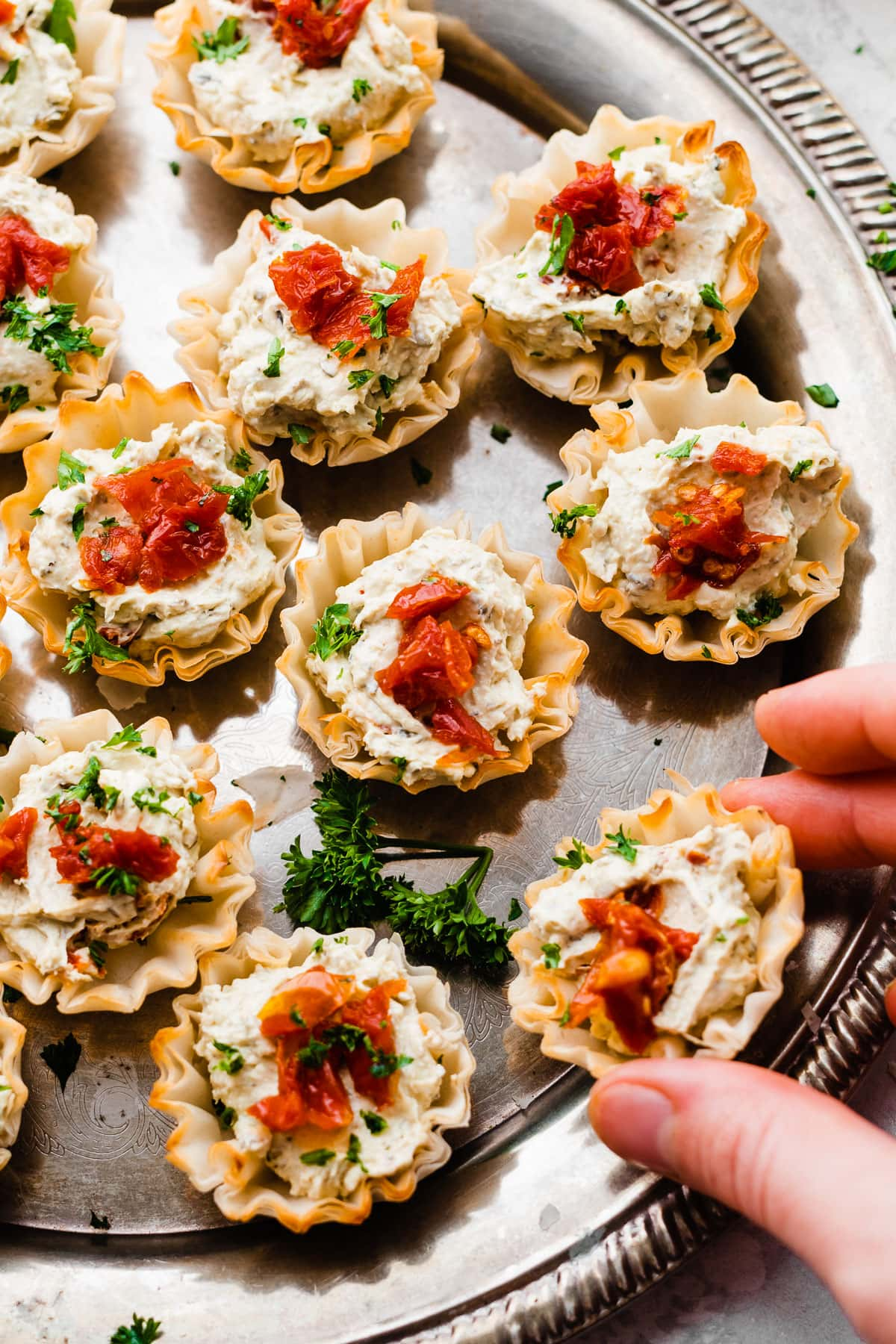 Sun Dried Tomato Pesto Bites are an easy appetizer recipe to have on hand for any part. Cream cheese pesto filling in phyllo dough with tangy sun dried tomatoes on top. Yum!