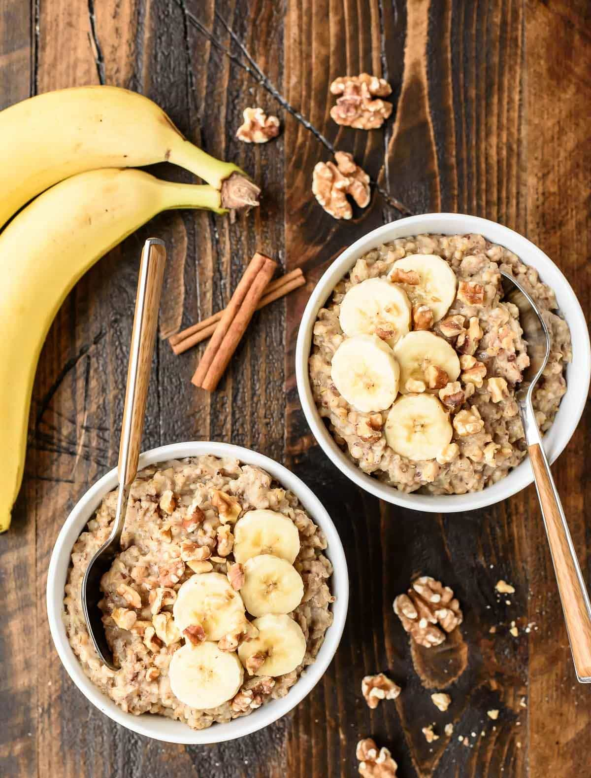 2 bowls of overnight steel cut oats next to fresh bananas and cinnamon sticks