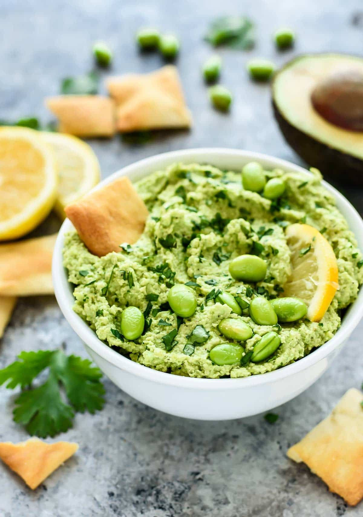 Rich, creamy hummus made with avocado and NO tahini! With edamame, avocado, and fresh lemon and garlic, this hummus recipe is loaded with super foods and is a great healthy dip, healthy snack, and sandwich spread too! @wellplated
