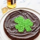 Chocolate, booze and sprinkles! A decadent, rich flourless chocolate cake with WHISKEY. Includes FREE PRINTABLE to make the cute sprinkle shamrock on top. A must make St. Patrick's Day dessert! Easy, gluten free, and so delicious. @wellplated