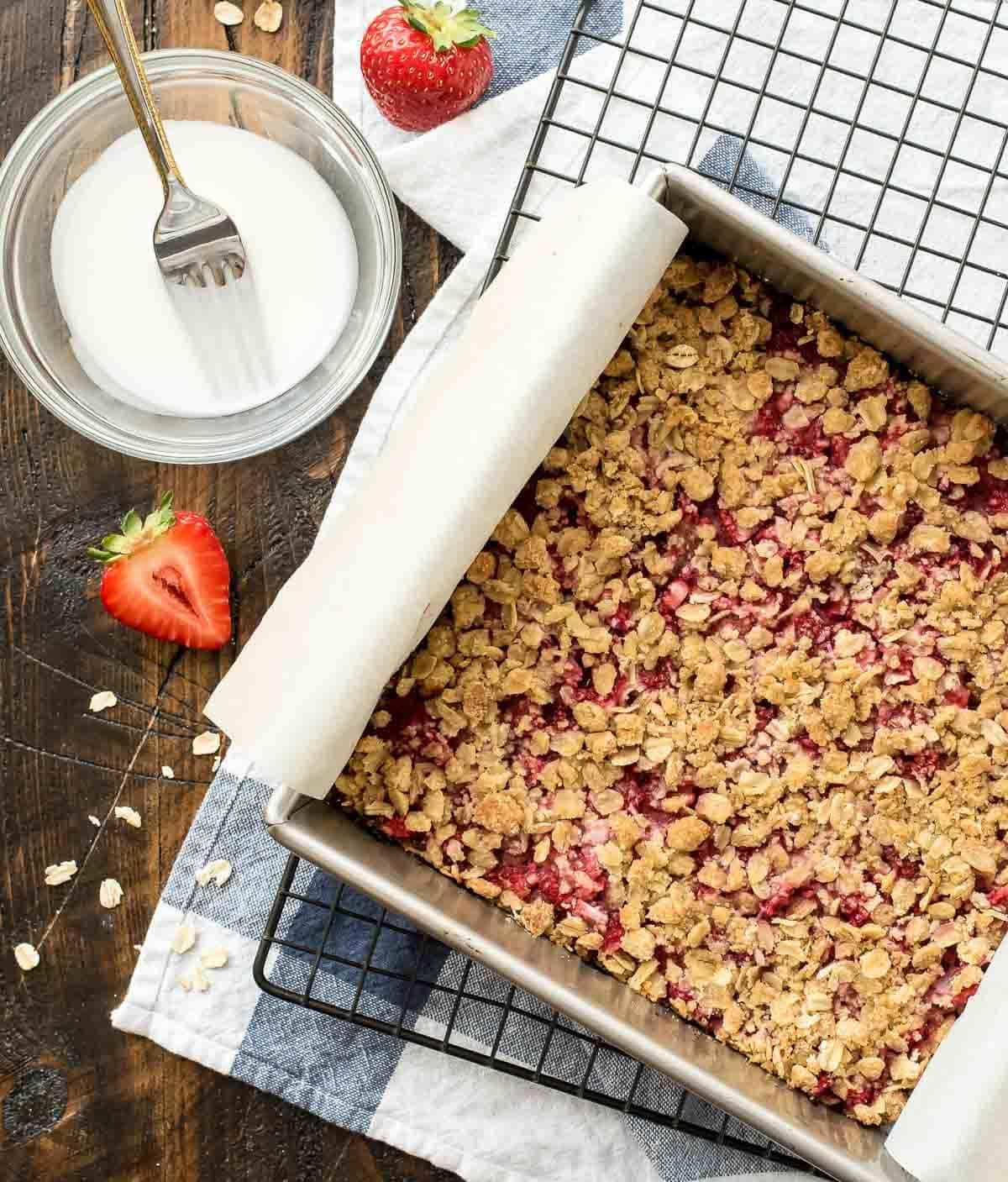 Strawberry Crumb Bars recipe — with a buttery crust, sweet fresh strawberry filling, butter crumb topping, and vanilla glaze, these bars have it all and are so easy! Made with 100% whole grain and the natural sweetness of strawberries, they are healthy enough for a snack but make a wonderful dessert bar for a party or picnic too! @wellplated