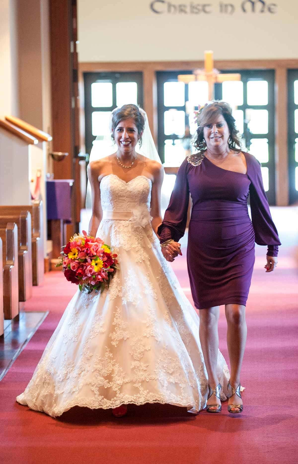 Mom walking daughter down the aisle at wedding.