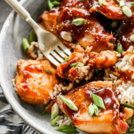 plate of crock pot bourbon chicken served over fluffy white rice