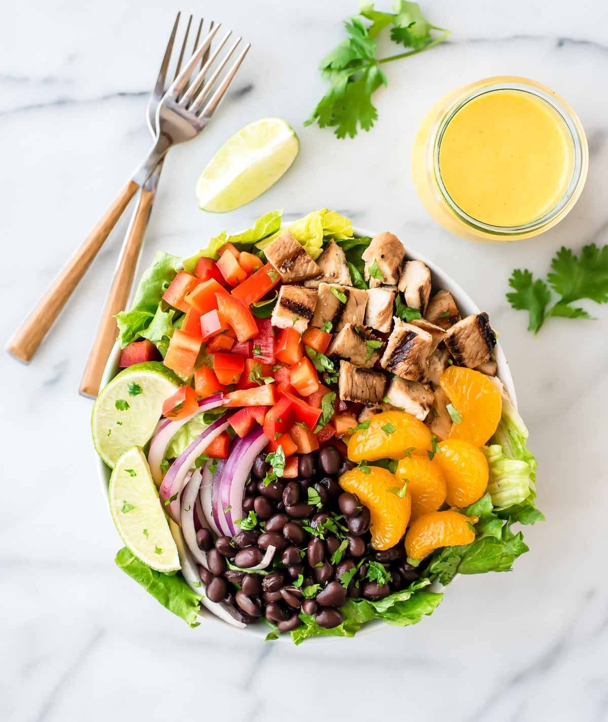 Grilled Caribbean Chicken Salad with 5 Minute Mango Dressing – Packed with juicy chicken, crunchy veggies, sweet oranges, and black beans. Super filling and DELICIOUS. The mango dressing is intoxicating! @wellplated