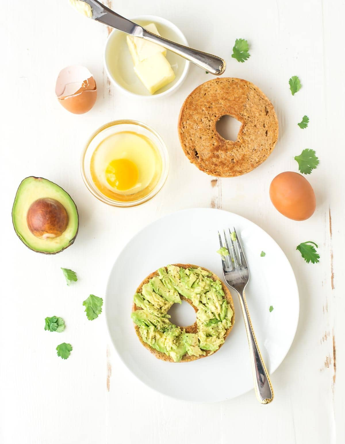 Egg in a Hole Recipe, made with a bagel and avocado - buttery toasted bagel with a fried egg in the center and smashed avocado on top. @wellplated
