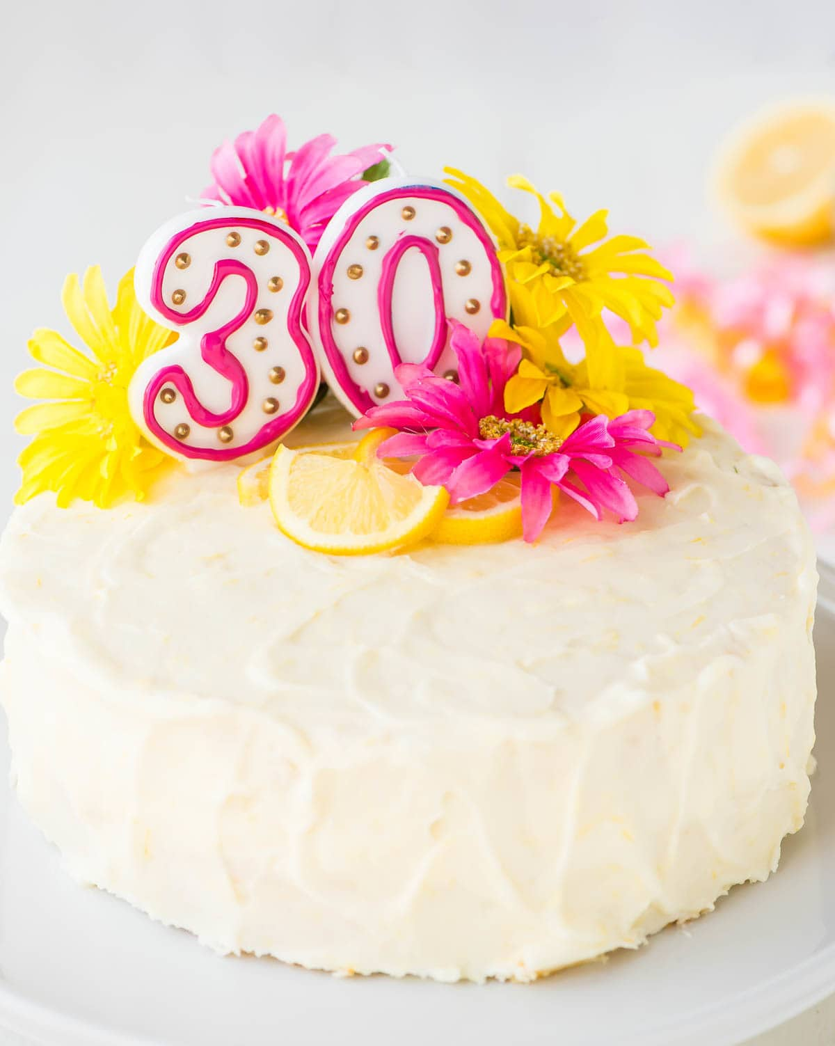 lemon layer cake decorated with fresh yellow and pink flowers and candles for a 30th birthday