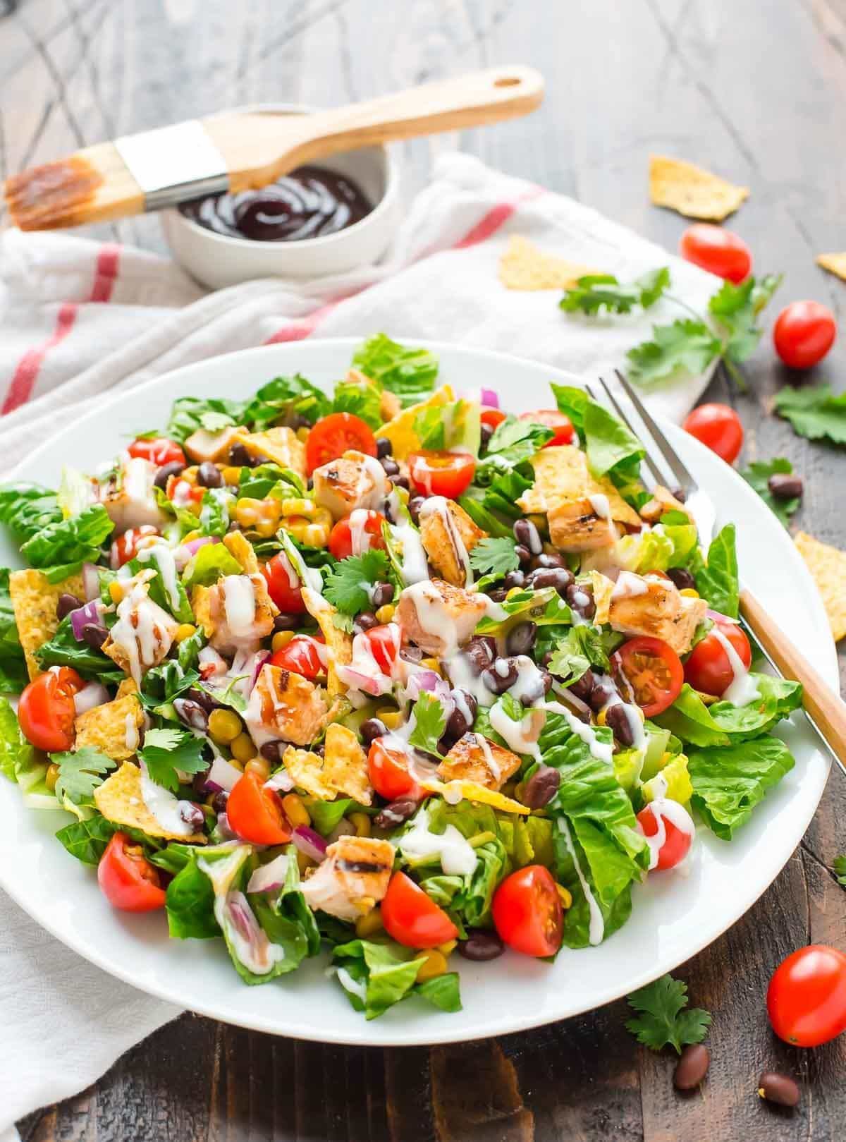 This BBQ Chicken Salad recipe is so fresh, filling, and healthy too! With light ranch, juicy grilled chicken, crunchy tortilla chips, and black beans. Our whole family loves it! @wellplated