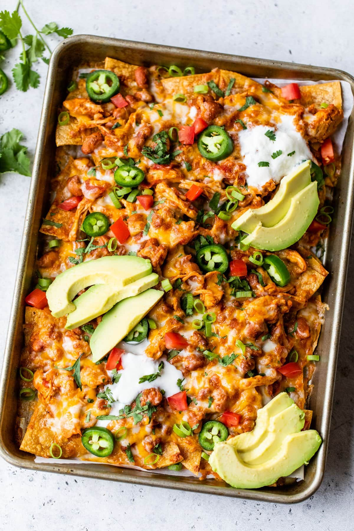 These Crock Pot Chicken Healthy Nachos are so quick and easy to make in the slow cooker. Perfect appetizer for a party, but healthy and filling enough for a weeknight meal! @wellplated