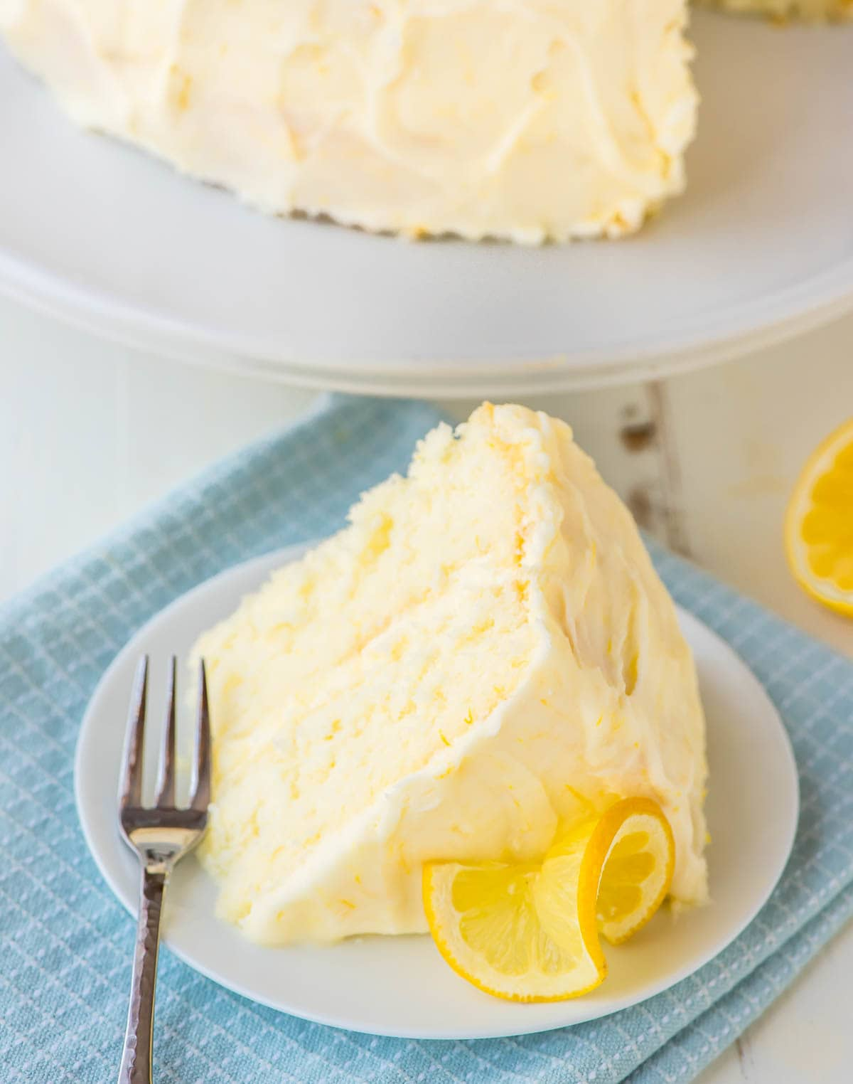 slice of lemon layer cake with lemon cream cheese frosting on a white dessert plate