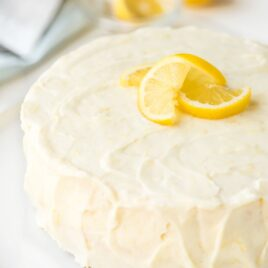 lemon layer cake frosted with lemon cream cheese frosting, garnished with lemon slices