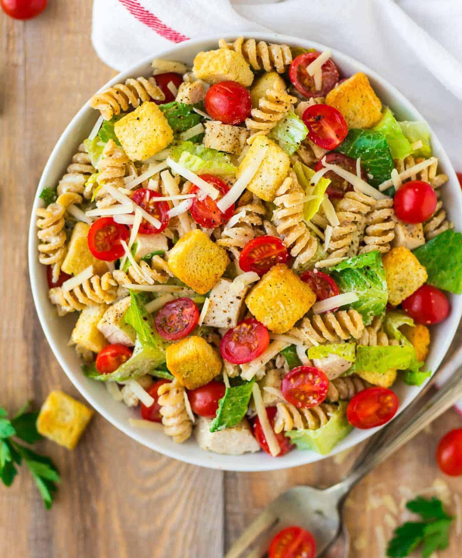 Healthy Chicken Caesar Pasta Salad in a bowl on butcher block.