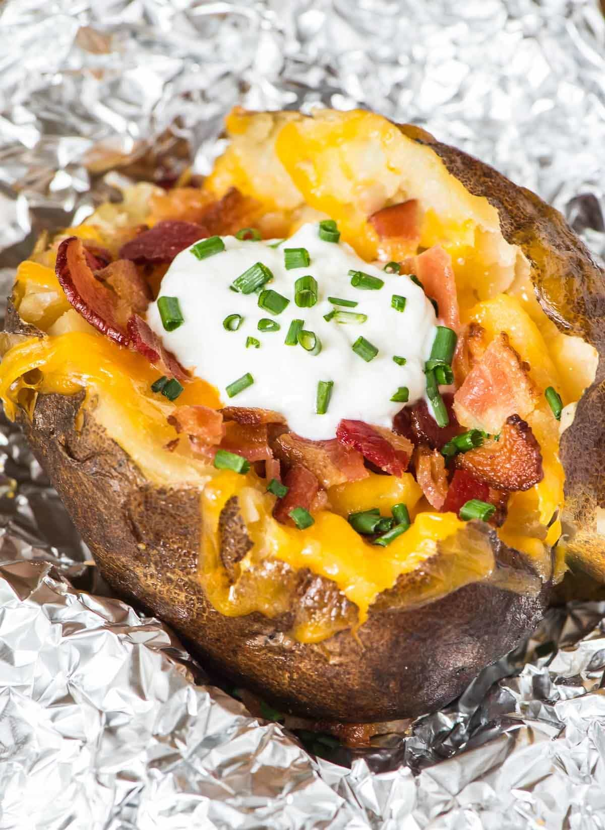 How to bake potatoes in a crock pot. The easiest way to bake a potato! They turn out perfectly fluffy every time and the slow cooker does the work. Great idea for an easy dinner or even to feed a crowd. @wellplated
