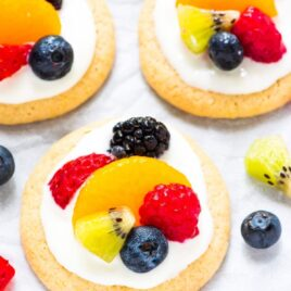 Fruit Pizza Cookies. A mini version of classic fruit pizza! Soft, buttery sugar cookies topped with sweet cream cheese frosting and fresh fruit. The perfect summer dessert! @wellplated