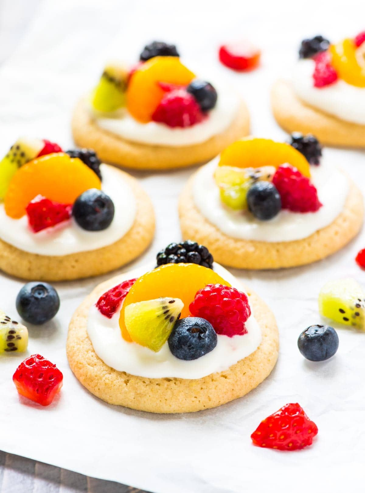 Mini Fruit Pizza Cookies — so fun and cute! Buttery lemon sugar cookies topped with sweet cream cheese frosting and fresh fruit. Easy to make and perfect for summer. @wellplated