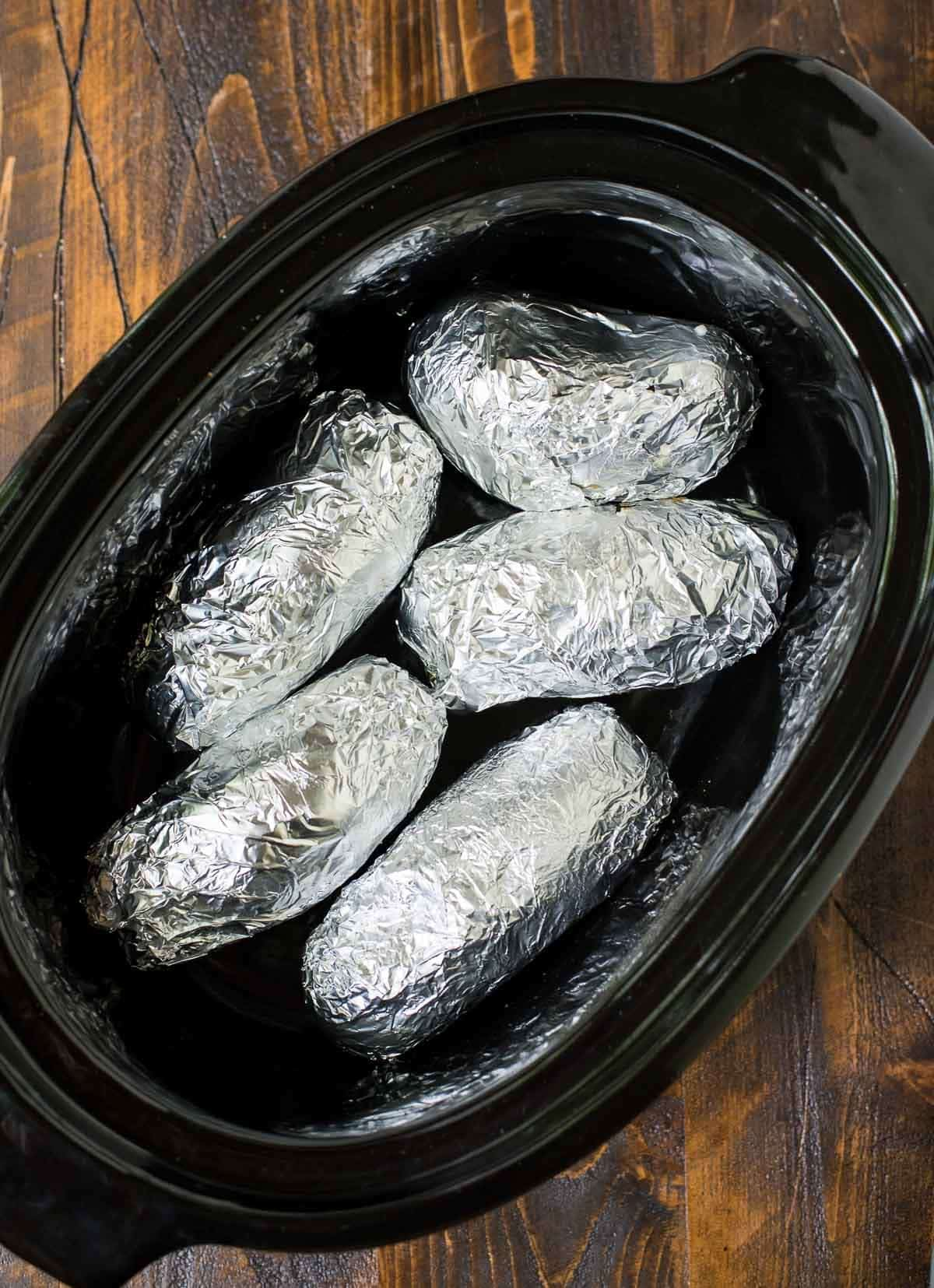 This trick to make Crock Pot Baked Potatoes is brilliant! Fluffy, delicious baked potatoes. No need to heat up your kitchen with this easy slow cooker baked potatoes recipe. @wellplated