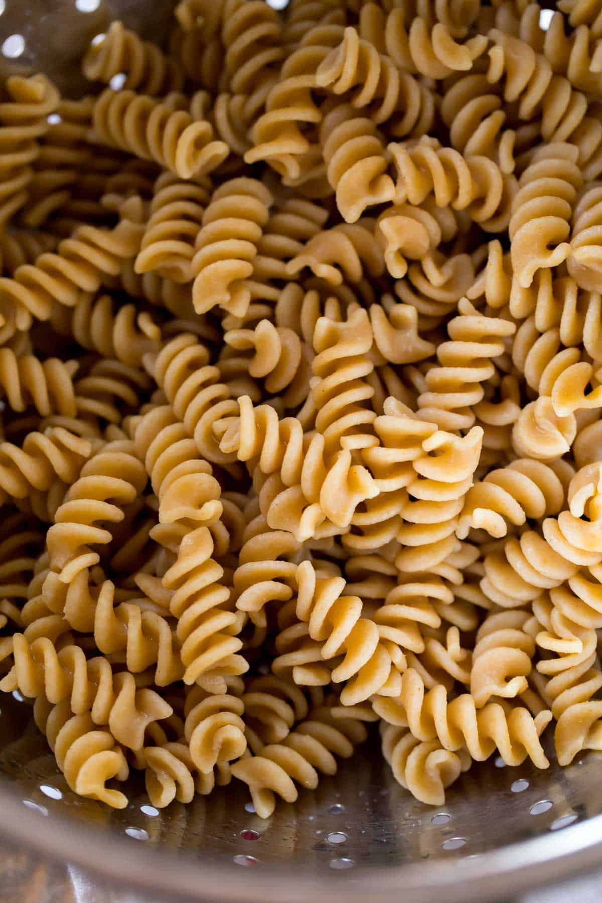 Cooked whole wheat pasta in a colander.