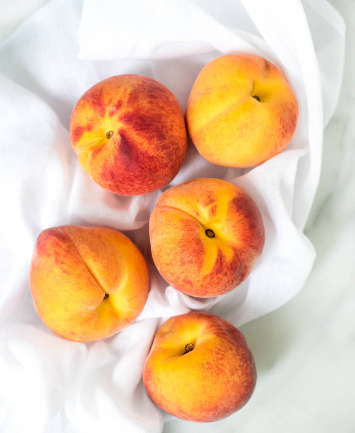 Crock Pot Peach Cobbler recipe — EASY and DELICIOUS summer dessert. Like a dump cake, you just toss the ingredients into your slow cooker. The crockpot does the work, and it tastes amazing! @wellplated