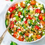 bowl of Israeli pearl couscous salad with a serving spoon in it