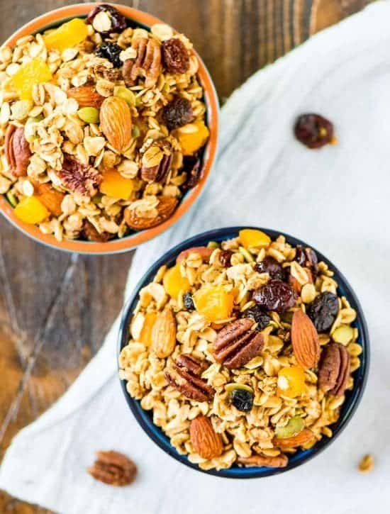 bowls of healthy clean eating granola with maple syrup, nuts, dried fruit, flax seeds, and roll oats