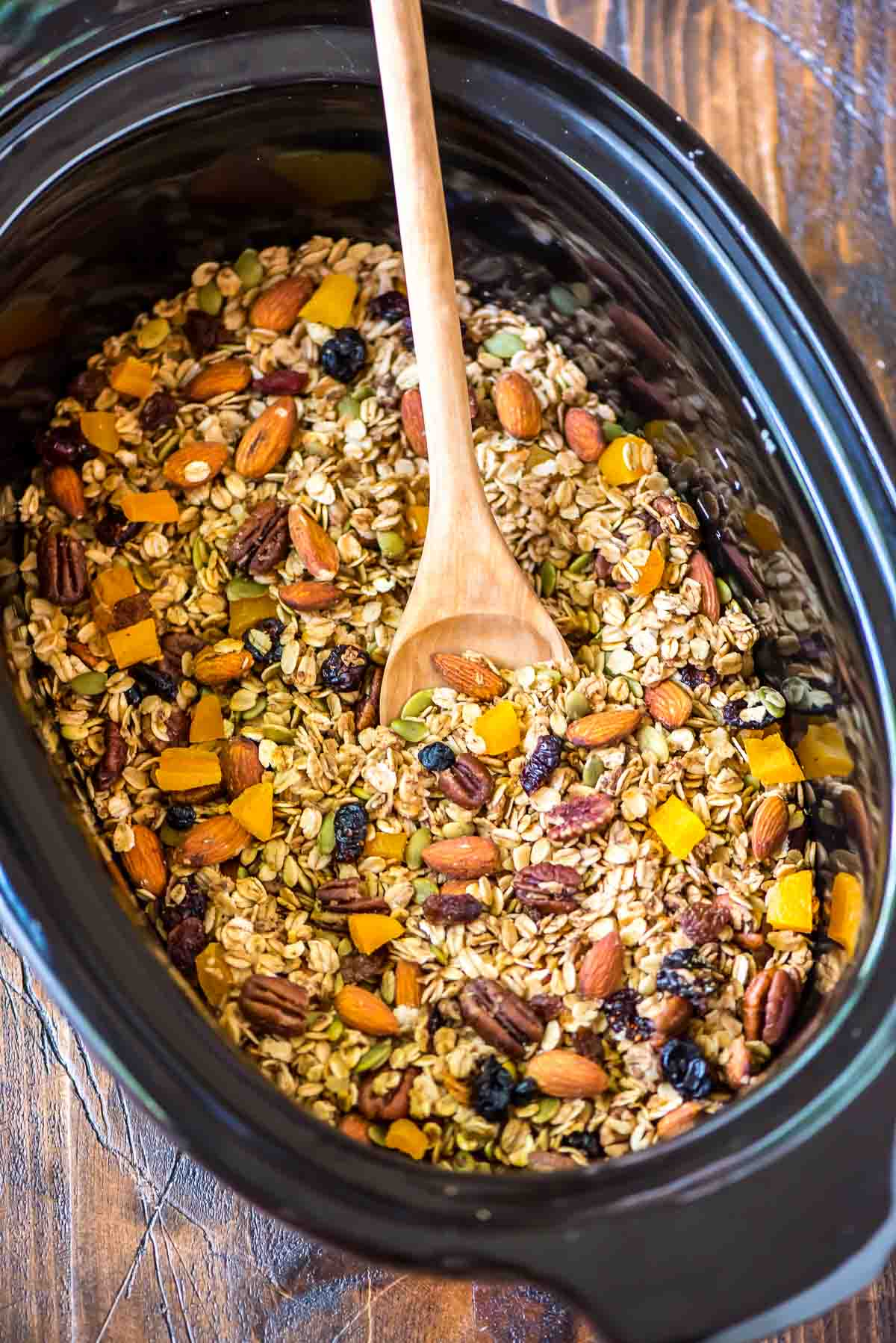 batch of healthy gluten free granola in a crock pot being stirred with a wooden spoon