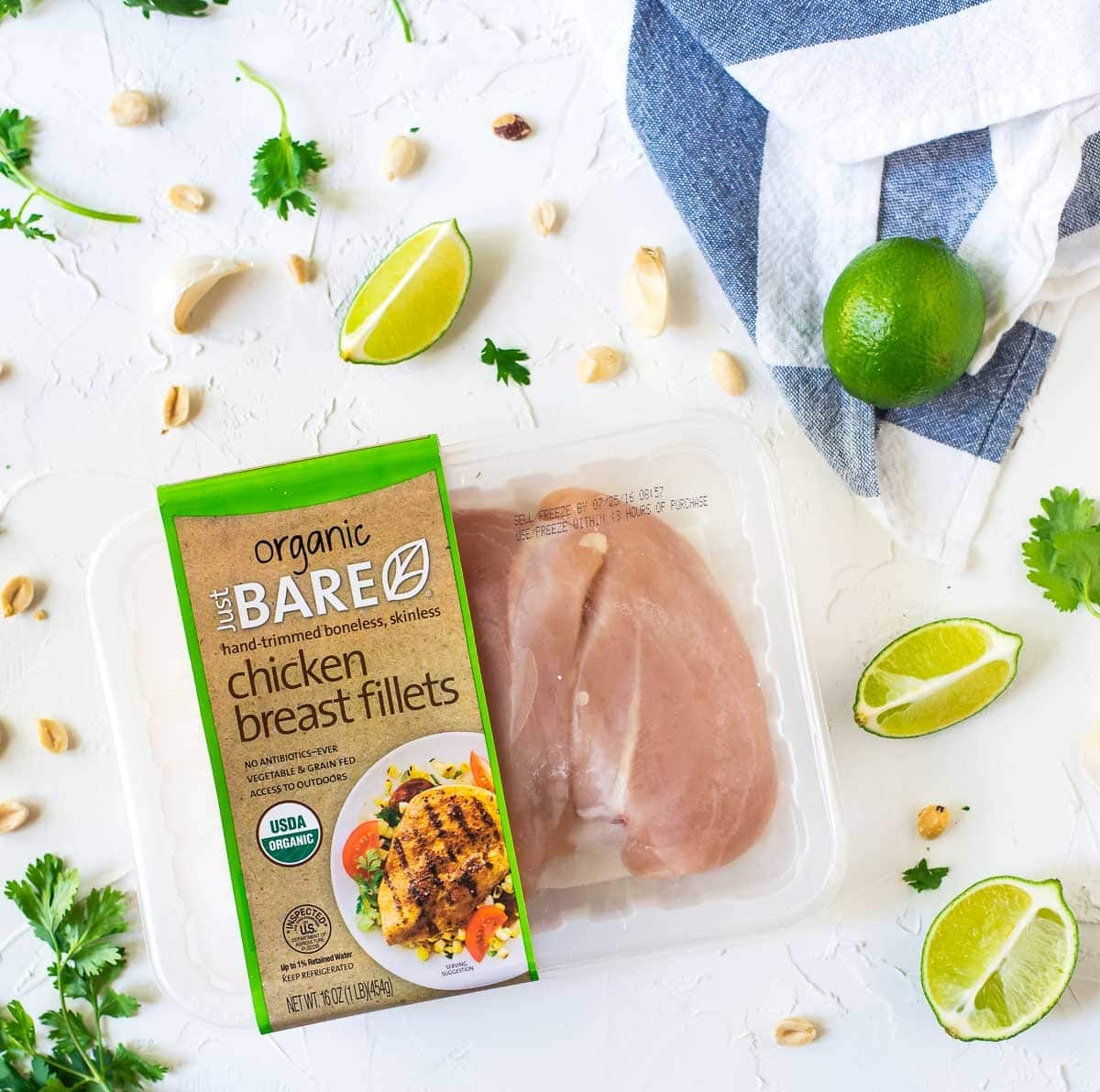 package of organic chicken breast fillets from Bare Organics surrounded by fresh lime wedges and peanuts