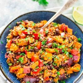 Roasted Sweet Potato Quinoa Black Bean Salad in a large blue serving bowl with a serving spoon in the dish.