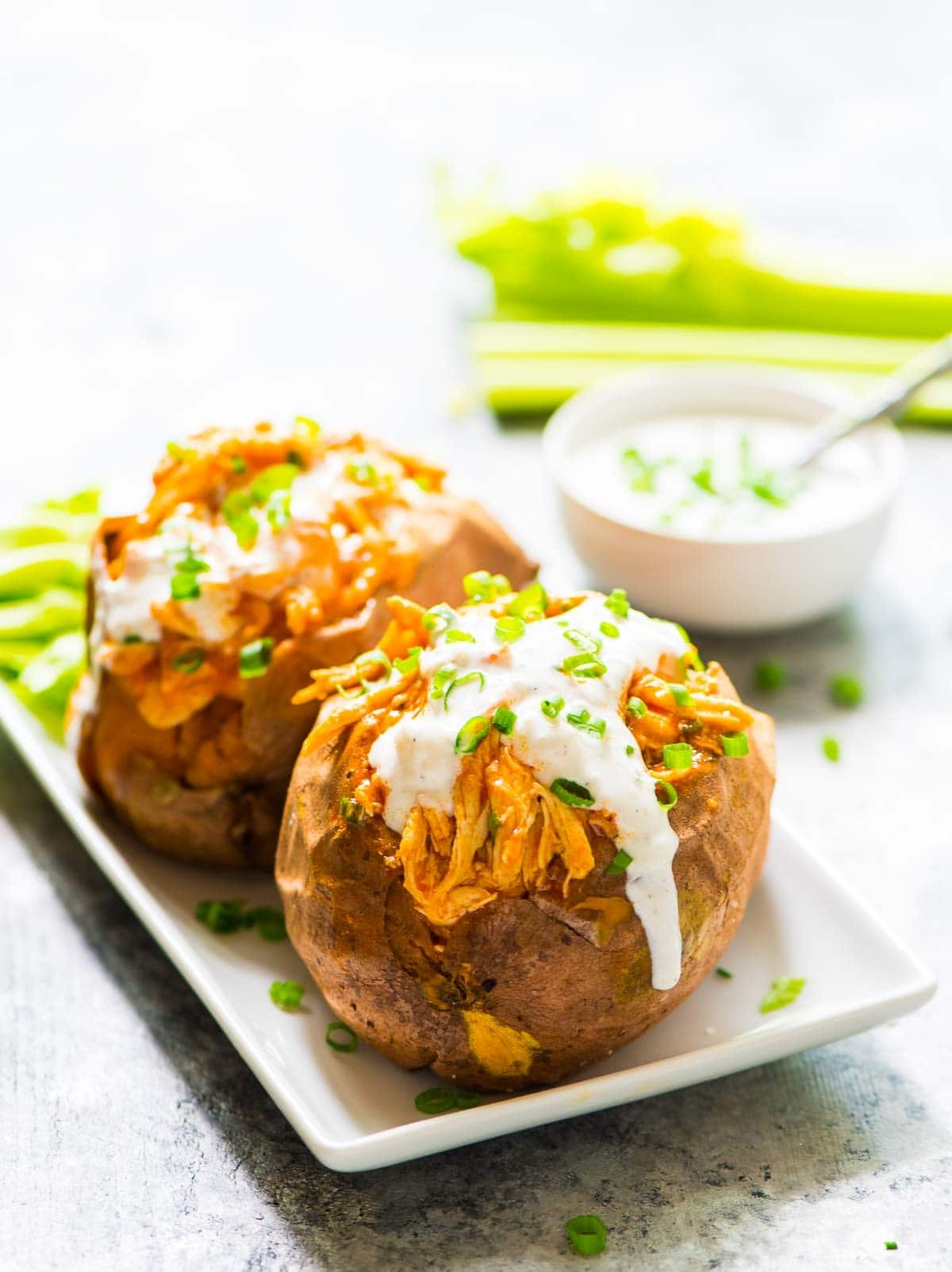 two sweet potatoes stuffed with a healthy Buffalo chicken dinner made in a crock pot