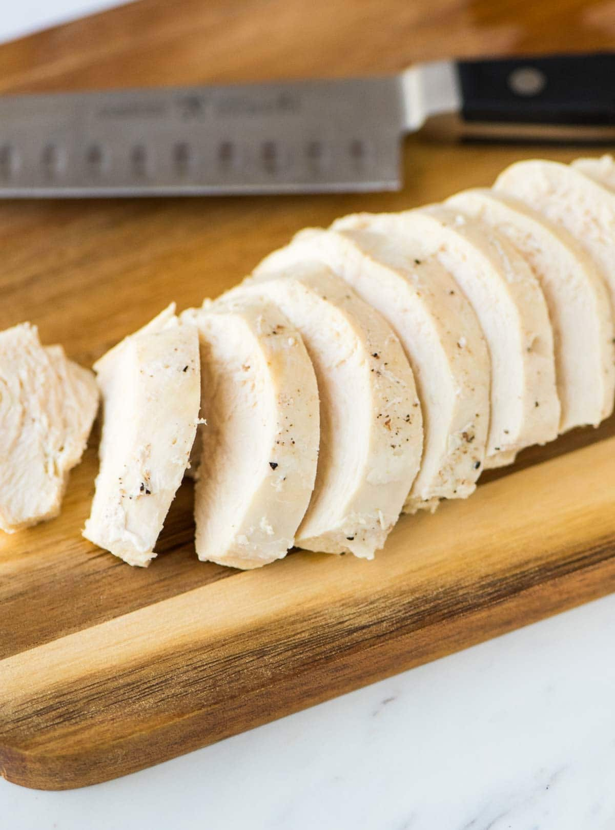cutting board with sliced chicken breast