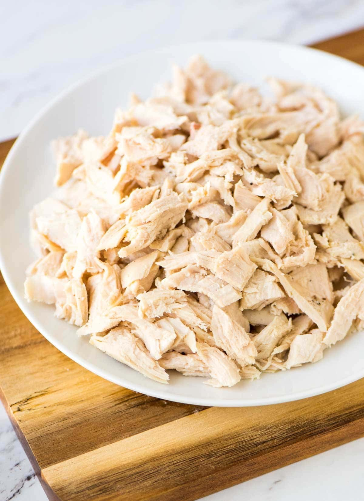 How to make shredded chicken. Use this easy method anytime a recipe calls for diced or shredded chicken. Perfect for adding to chicken salad, chicken enchiladas, and more! @wellplated
