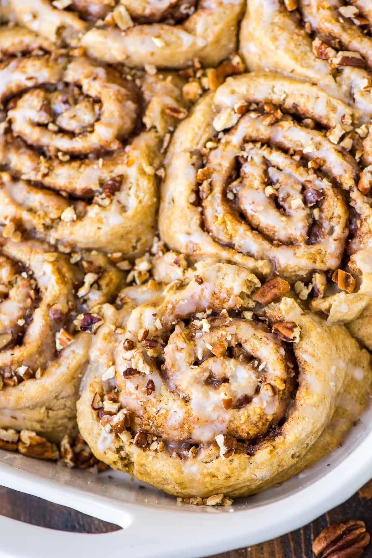 The BEST Homemade Biscuit Cinnamon Rolls. Easy recipe with no rising! Fluffy buttermilk biscuit dough, filled with gooey cinnamon sugar and topped with buttermilk glaze and toasted pecans. TO DIE FOR. Recipe at wellplated.com | @wellplated