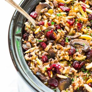 Crock Pot Wild Rice Stuffing with Cranberries and Almonds. Gluten free and DELICIOUS. Easy to make ahead, and the slow cooker frees up the oven so it's perfect for Thanksgiving, Christmas, or anytime you are hosting a crowd. Recipe at wellplated.com | @wellplated