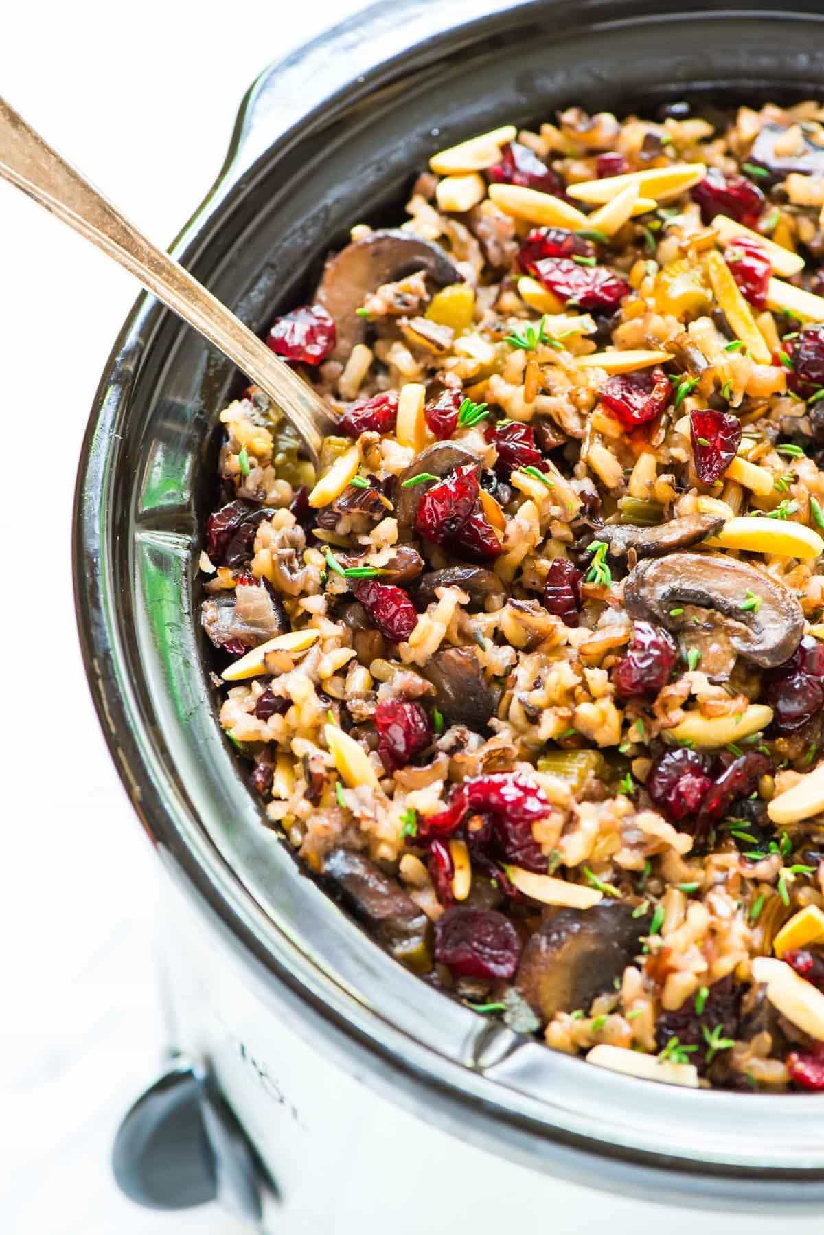 Crock Pot Wild Rice Stuffing with Cranberries and Almonds. Gluten free and DELICIOUS. Easy to make ahead, and the slow cooker frees up the oven so it's perfect for Thanksgiving, Christmas, or anytime you are hosting a crowd. Recipe at wellplated.com   @wellplated