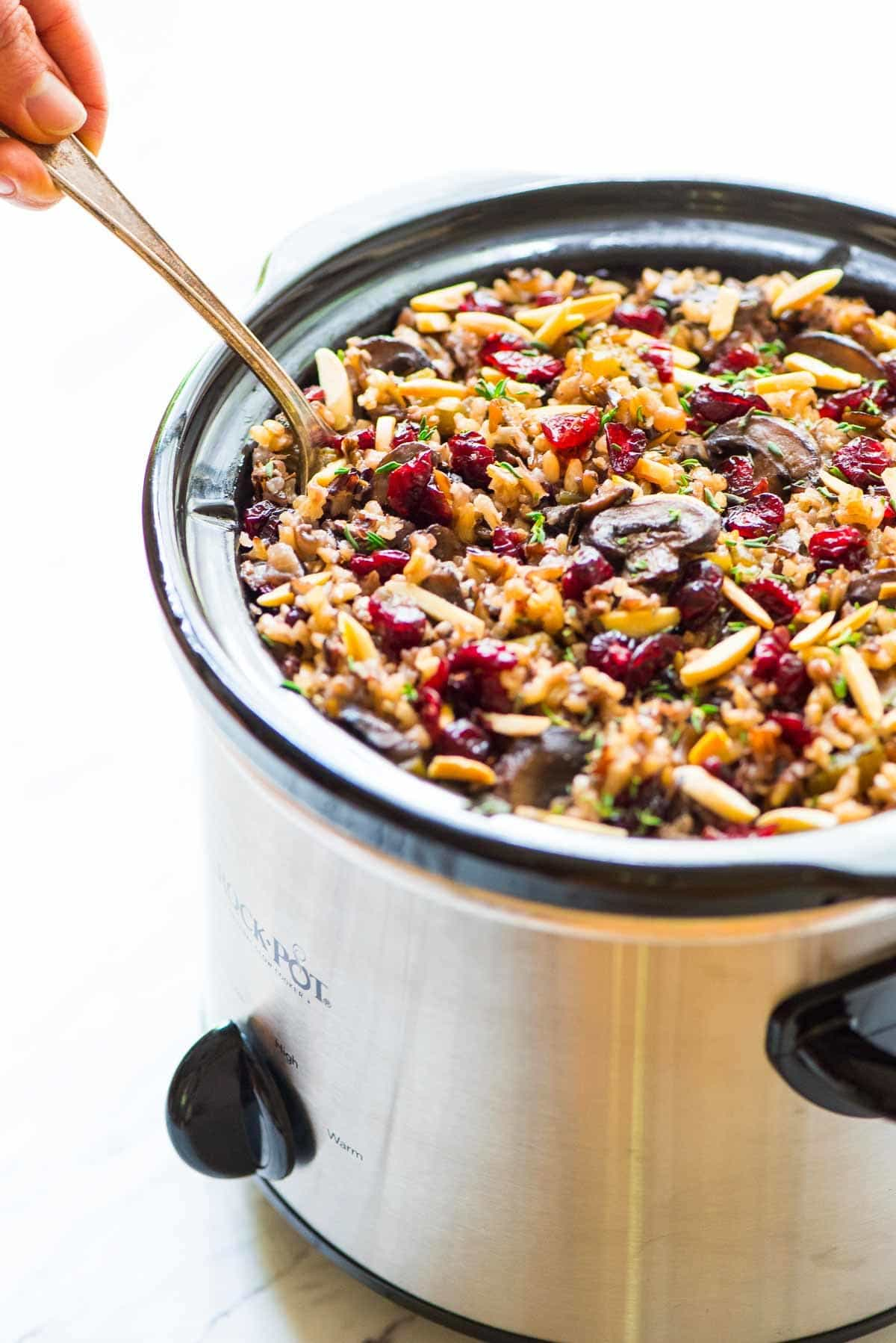 The BEST gluten free stuffing: Crockpot Stuffing with Wild Rice, Cranberries and Almonds. Easy slow cooker recipe that our whole family loved! Can be made ahead and frees up the oven, so it's the perfect holiday and Thanksgiving side dish. {vegan, gluten free} Recipe at wellplated.com   @wellplated