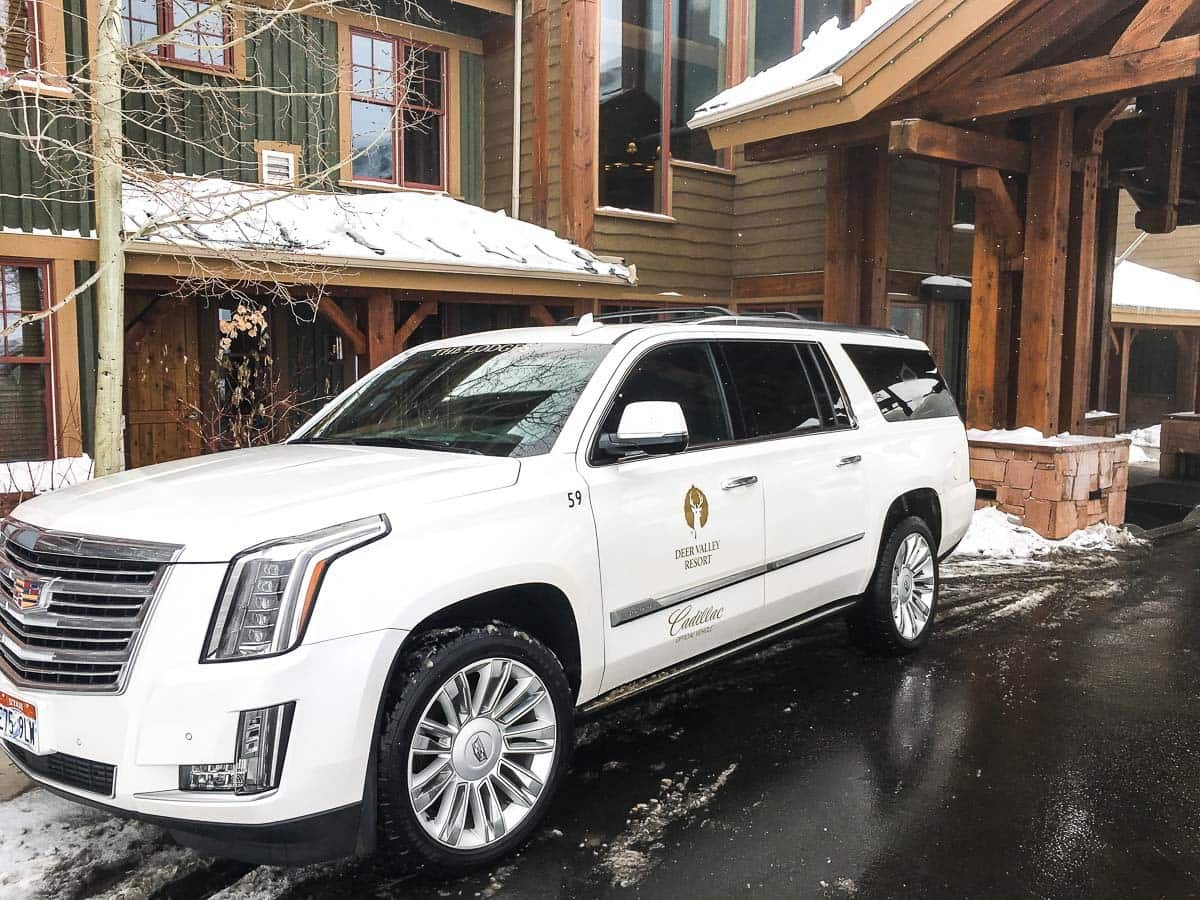 A Cadillac SUV parked outside a hotel