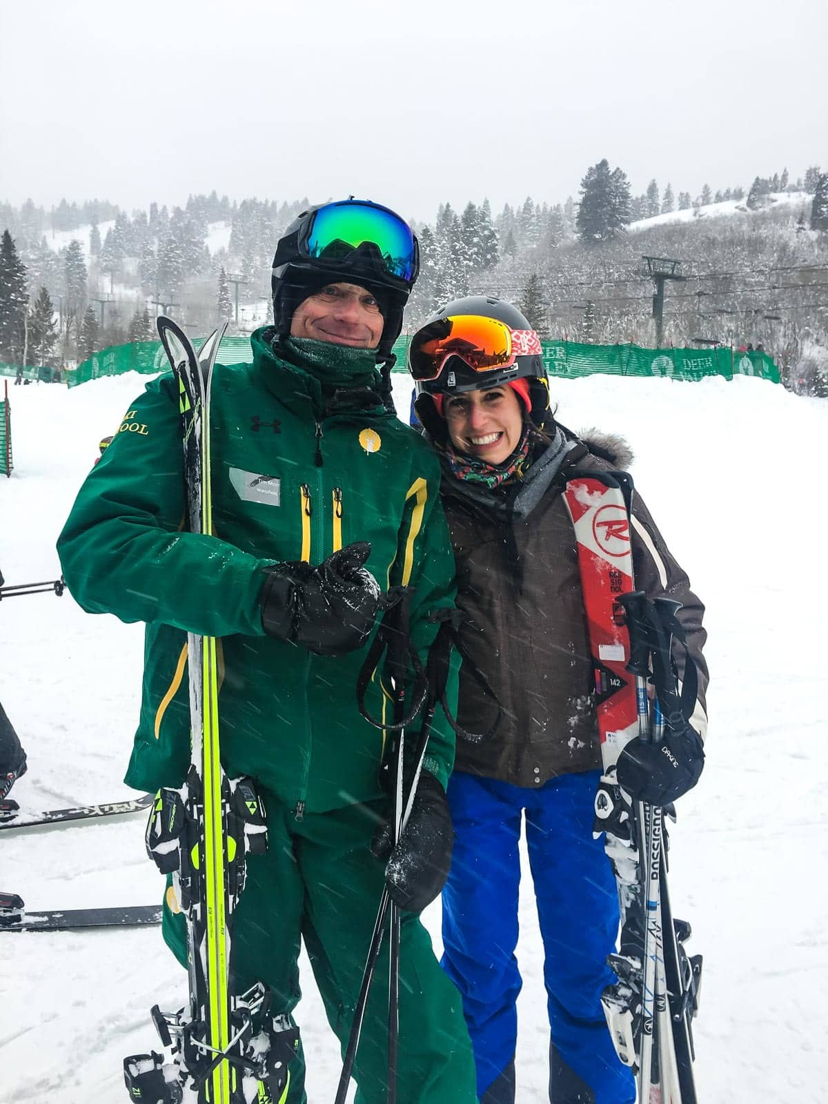 Erin and Ben Clarke in snow gear holding skiis