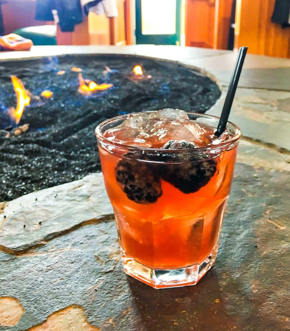 A cocktail next to a fire pit