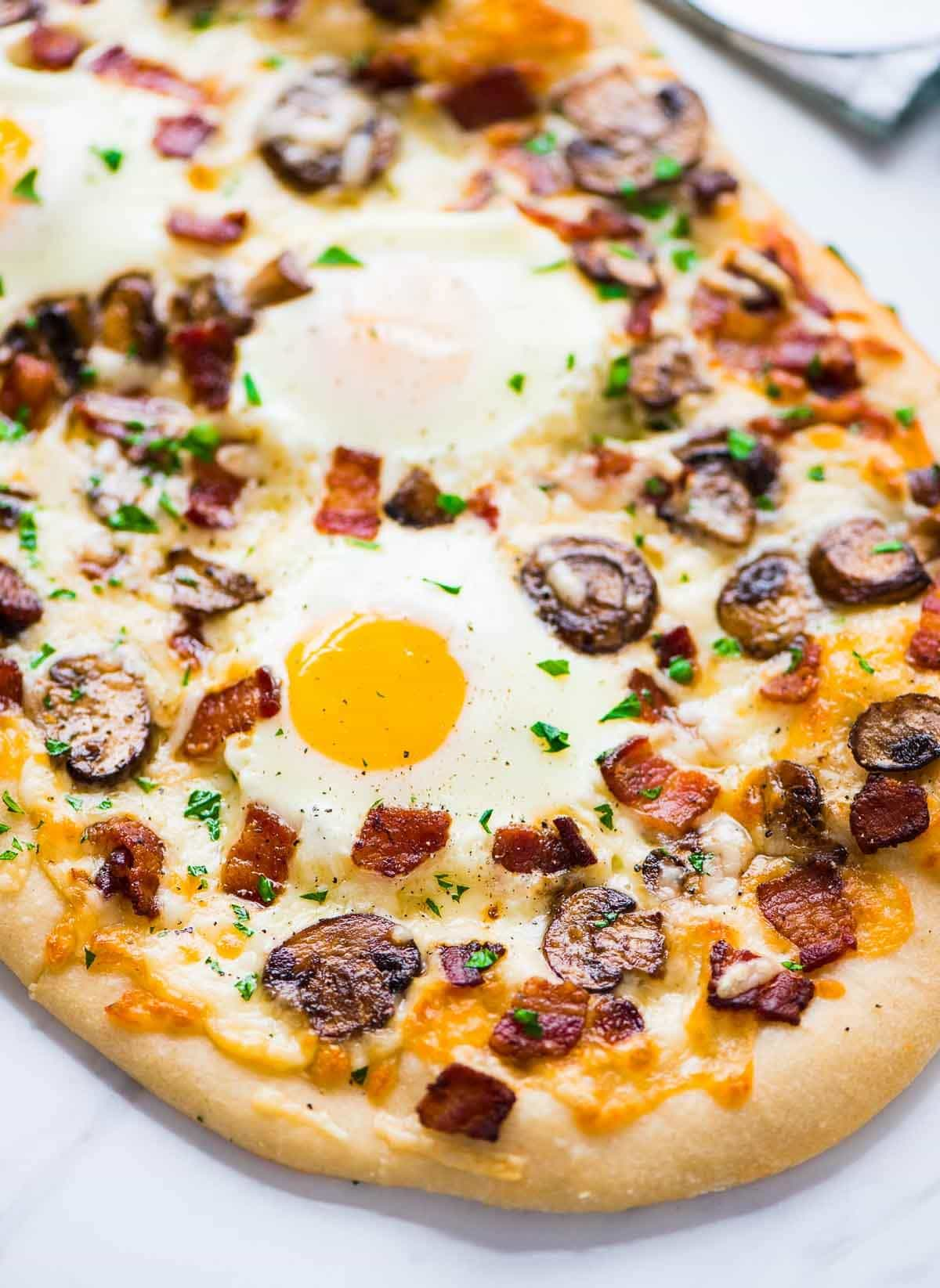 Carbonara Pizza with bacon, mushrooms, garlic, and a sunny side up egg. The bacon and yolk make this pizza absolutely irresistible! Recipe at wellplated.com | @wellplated