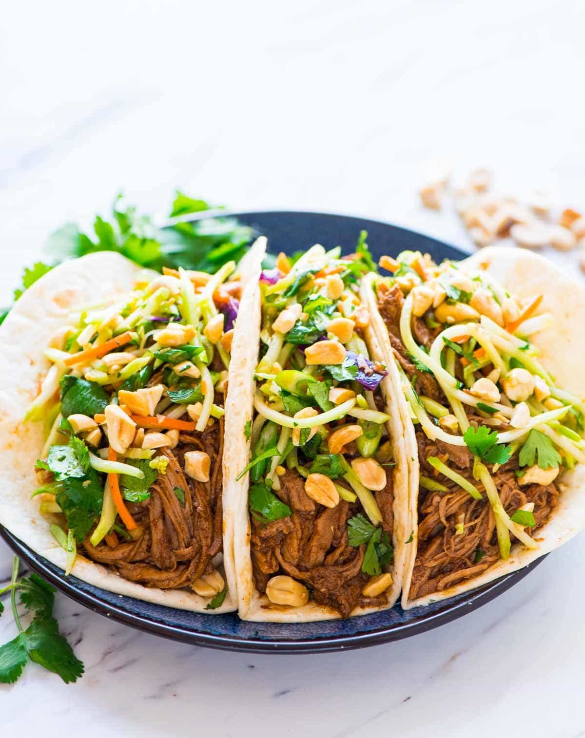 Asian Pulled Pork Tacos topped with crunchy peanut broccoli slaw.