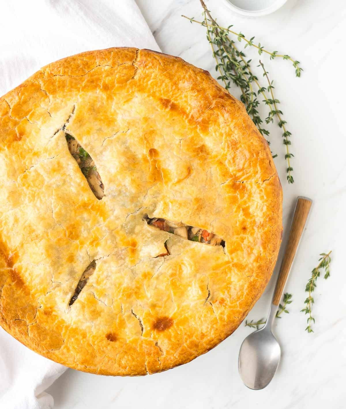Healthy chicken pot pie in a pie dish with fresh thyme