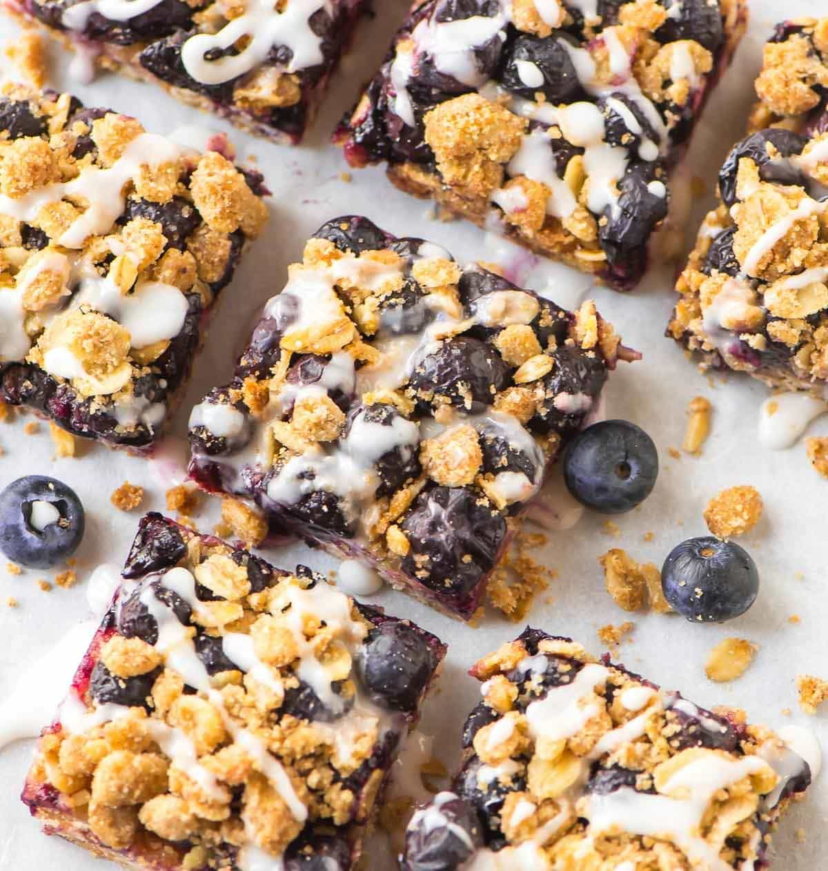 Healthy Blueberry Oatmeal Bars. Only 105 calories each! Fast, easy, no mixer required. Buttery and soft with butter brown sugar crumble and sweet vanilla glaze. Perfect healthy dessert or breakfast for busy mornings. Recipe at wellplated.com | @wellplated