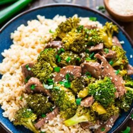 blue dinner plate of Asian beef and broccoli, made in a slow cooker